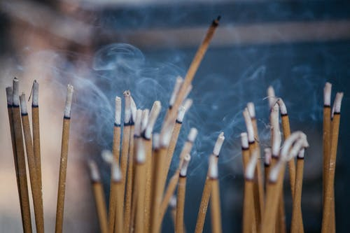 Various types of smoldering aroma sticks with smoke on stand in cozy apartment