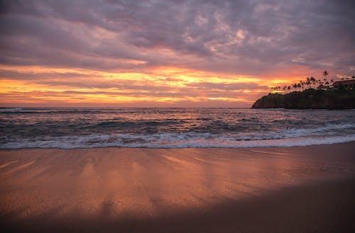 Foamy sea under bright sunset sky