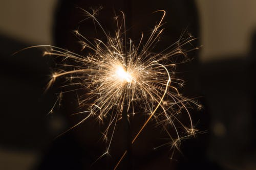 Closeup of thin glowing flame of burning sparkler in dark room at night