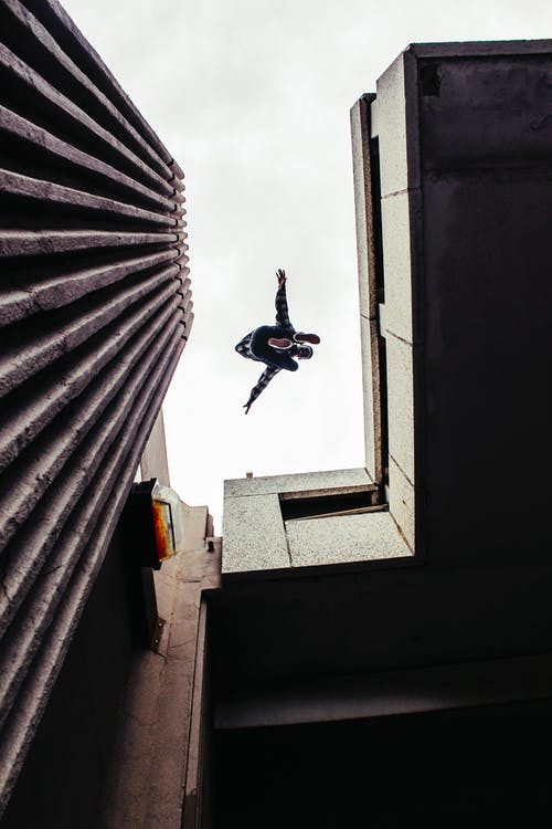 Man in Black Jacket and Blue Denim Jeans Jumping on Gray Concrete Building