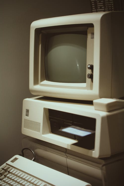 Retro obsolete white personal computer with small monitor and system unit with keyboard placed in room near gray wall