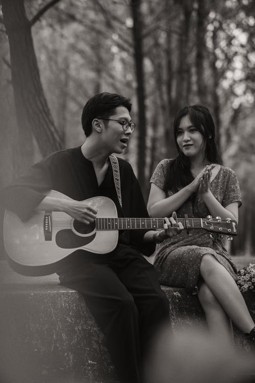 Black and white of talented Asian boyfriend playing acoustic guitar while sitting on barrier near girlfriend in nature during date