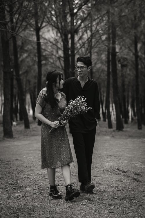 Asian couple walking in park