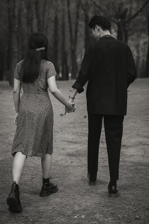 Black and white back view of unrecognizable loving couple holding hands while strolling in garden with tall trees in nature