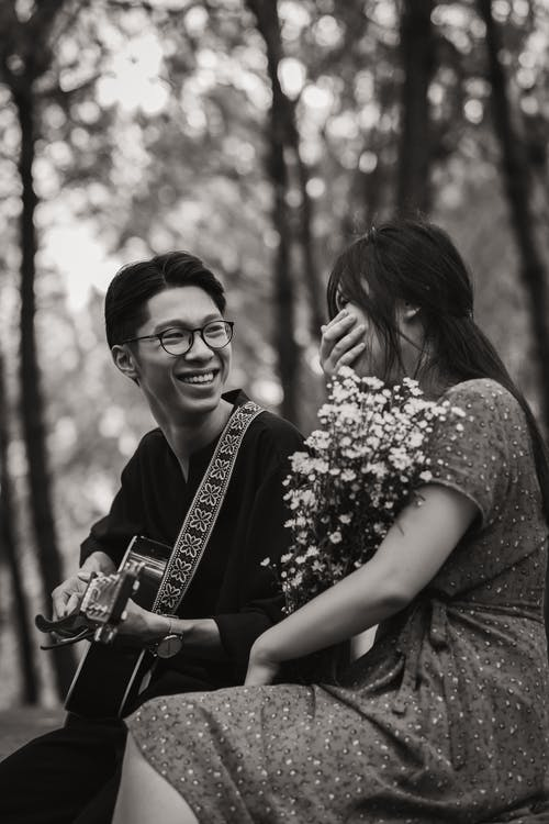 Asian couple with guitar in park