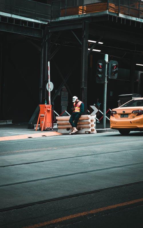Man in Black Jacket Sitting on Orange Car Hood