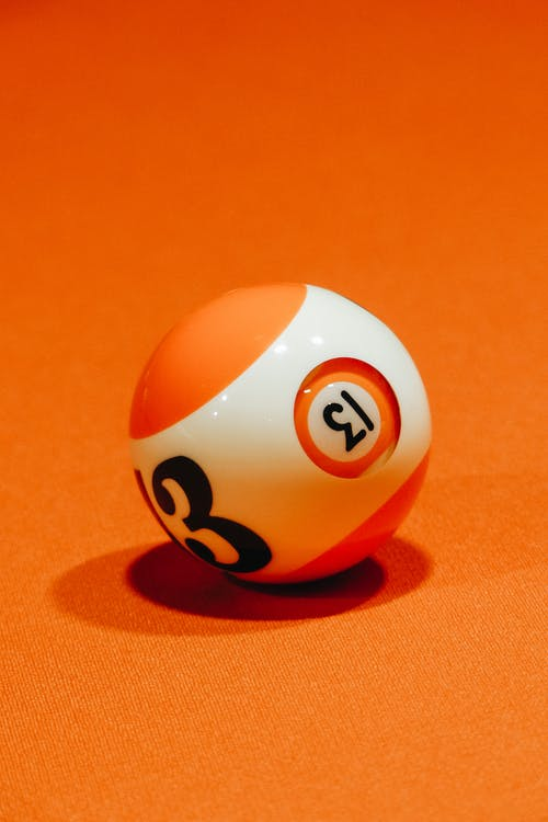 Billiard ball with number on bright orange surface for complex intellectual board game