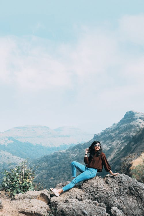 Full body of female hiker touching hair while sitting on peak of mountain with bent leg against rocky cliffs in highlands