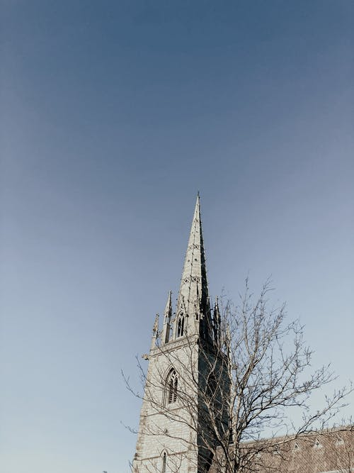Cathedral tower with spire against blue sky