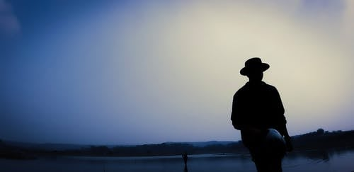 Silhouette of Man Standing Near Body of Water