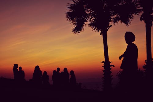 Silhouette of People Standing Under Orange Sky