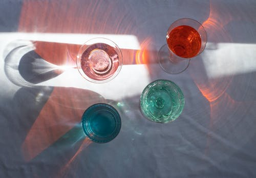 Top view of transparent glasses filled with different beverages and placed at sun beam