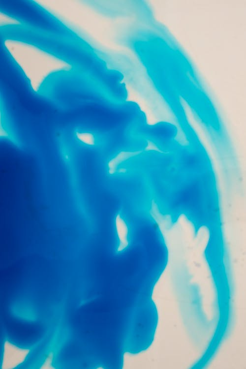 Abstract background of bright blue color ink diffusing slowly in clear water on white background