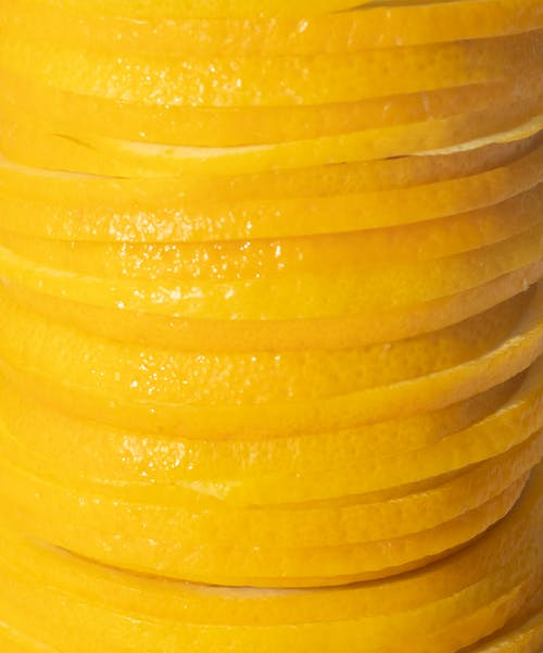 Full frame background of pile of sliced pieces of fresh juicy orange in closeup