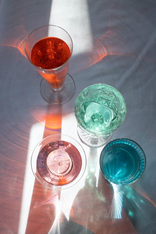 From above of crystal glasses filled with refreshing drinks on white table in sunlight