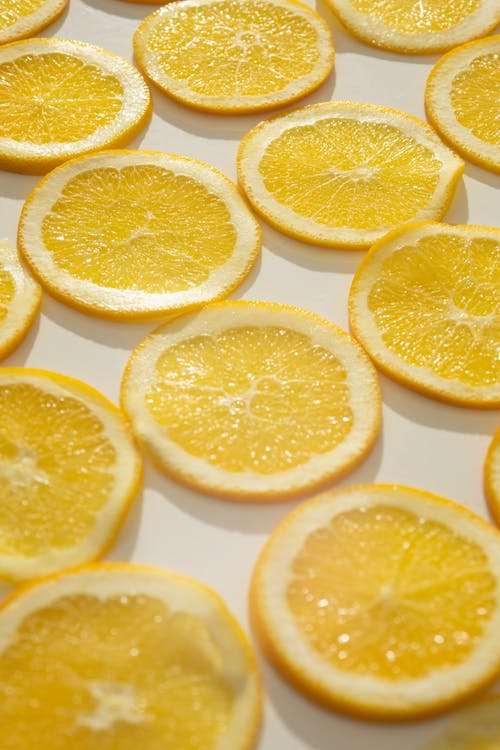 Background set of delicious fresh juicy orange slices placed on white surface in sunlgiht
