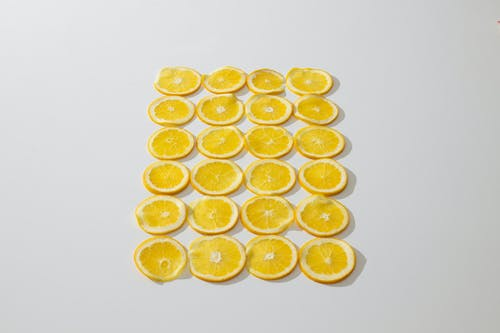 From above composition of fresh juicy oranges cut in slices and laid on white background