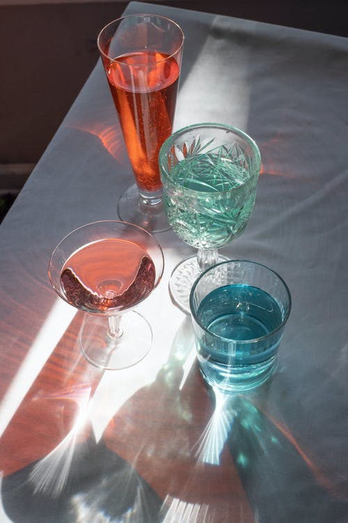 Crystal glassware filled with alcohol beverages and served on table with white tablecloth in daylight