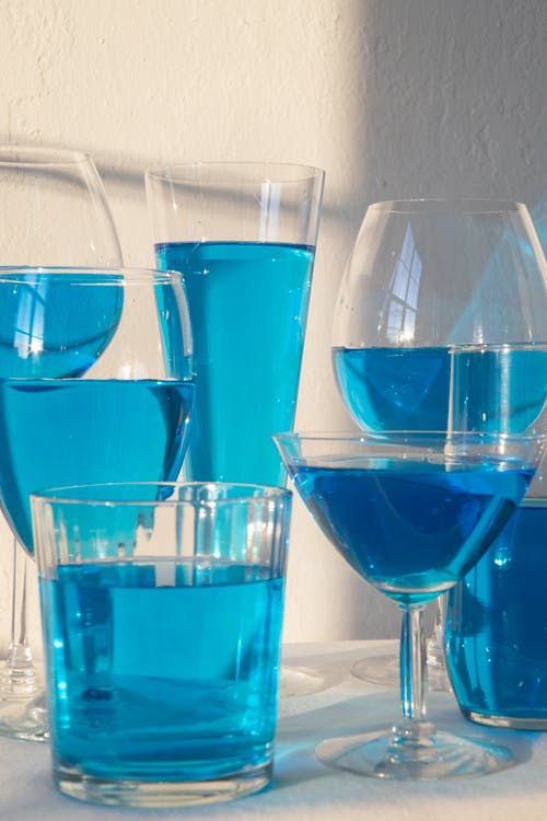 Composition of different crystal glasses filled with light blue beverage placed on table