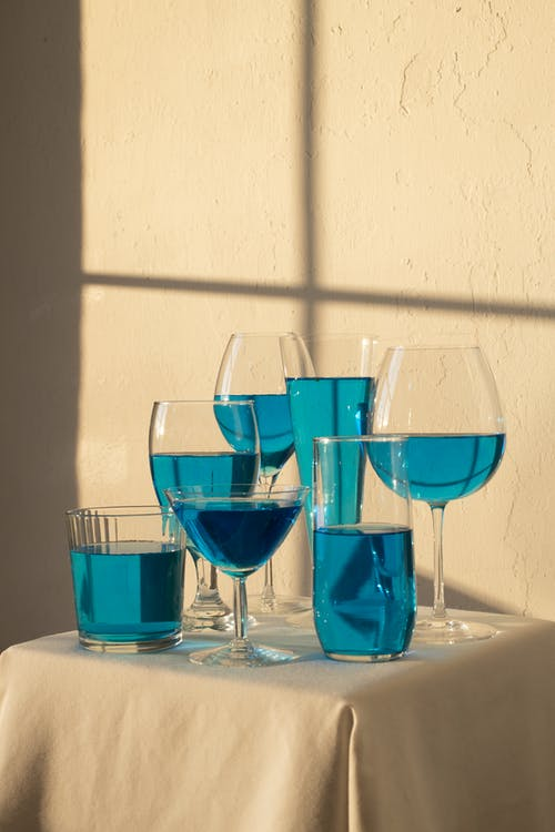 Arrangement of transparent glasses filled with blue drink and placed on table with white tablecloth