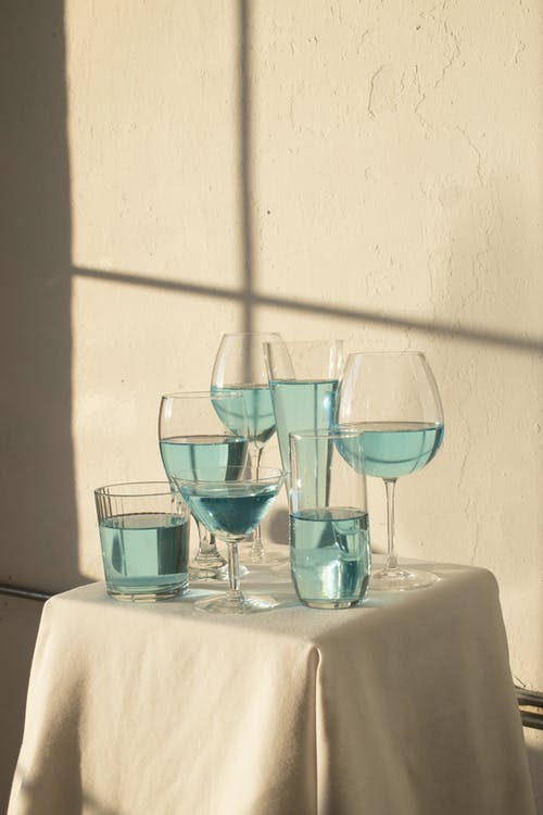 Set of various glasses filled with blue drink and placed on table