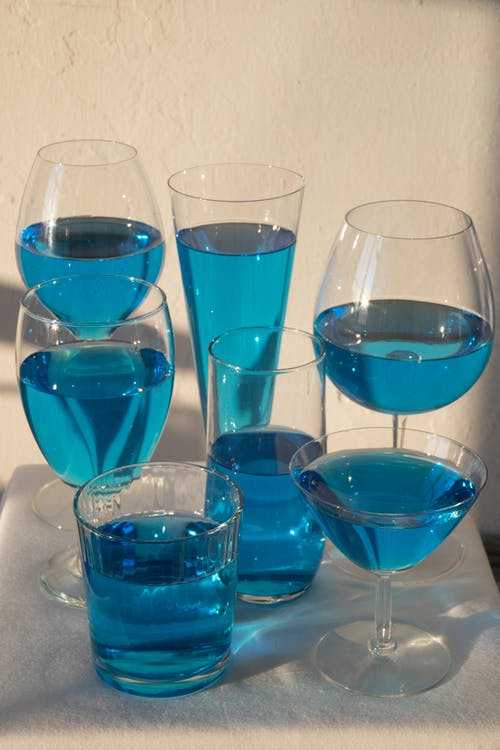 Arrangement of glassware filled with colorful alcoholic drink and placed on table against white wall