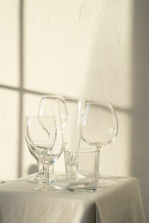 Composition of empty crystal glasses placed on table with white tablecloth in sunlight