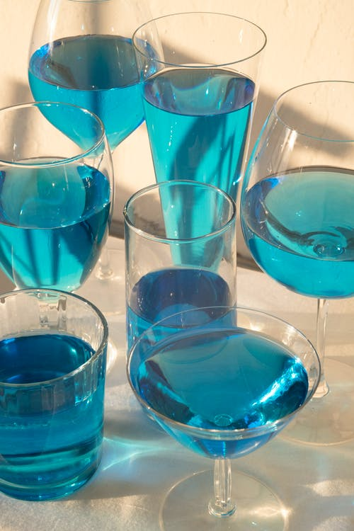 Glasses with blue alcoholic cocktails
