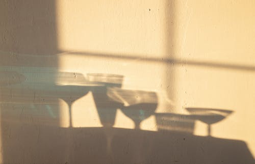 Shadows of different crystal glasses filled with drinks reflecting on white wall in sunlight