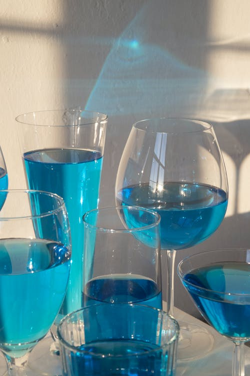 Closeup composition of crystal clear glasses filled with blue shaded drink in sunlight