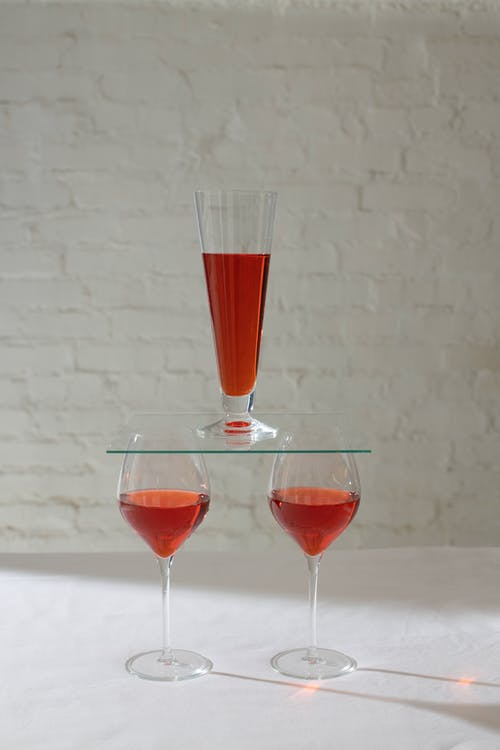 Arrangement of wineglasses filled with red alcohol drink placed on white table against brick wall in light room with shadows