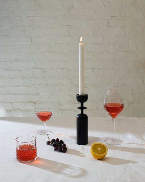 Arrangement of wineglasses and glass with alcohol drink placed on white table with burning candle and grapes against brick wall