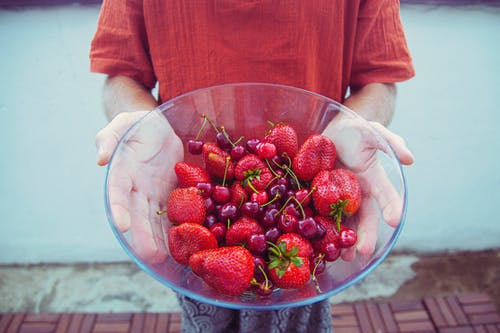 From above crop anonymous person in casual clothes demonstrating glass bowl filled with ripe yummy strawberries and cherries in backyard