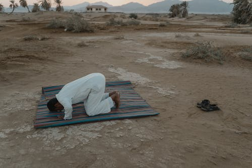 Photo Of Man Bowing On Mat During Dawn