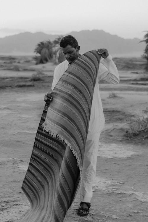 Man in White Dress Shirt Holding A Carpet