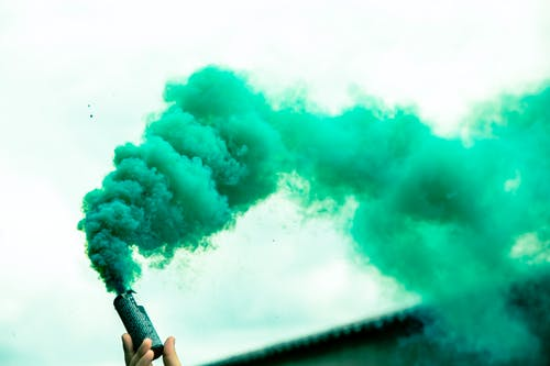 Crop person holding colorful smoke bomb