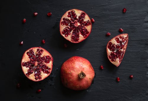 Close-Up Shot of Slices of Pomegranate on a Black Surface