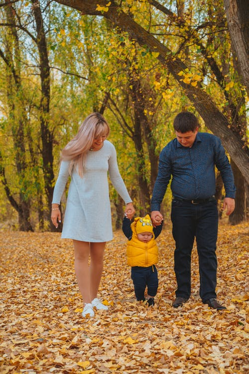 Full body of family holding hands while strolling on fallen leaves in forest during autumn weekend