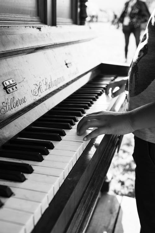 Black and white of crop unrecognizable musician standing on stage and performing melody on piano