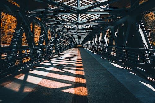 Empty footbridge in countryside under sunlight