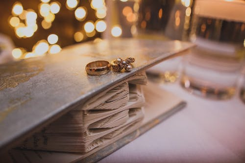 Golden wedding rings on decorated book in room for celebration with bright shiny lights