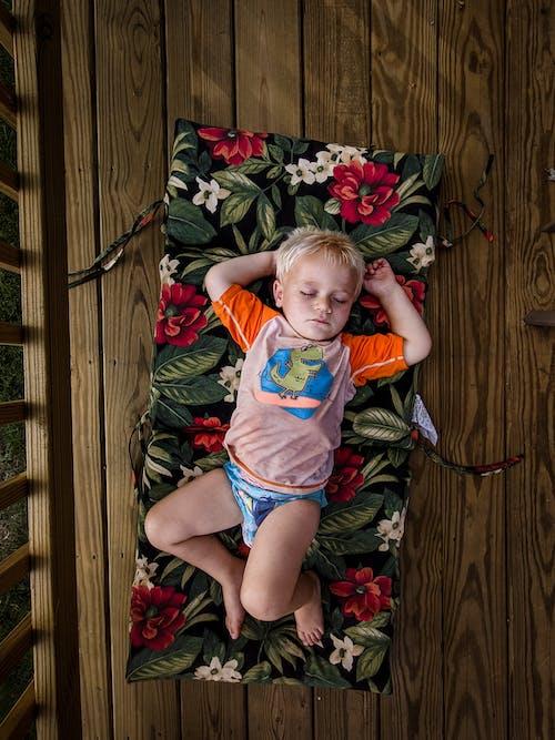 Cute little boy sleeping on mattress