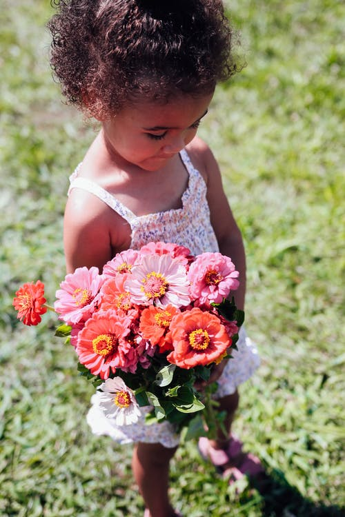 High angle of crop African American child in summer clothes standing on grass and holding bunch of fresh flowers