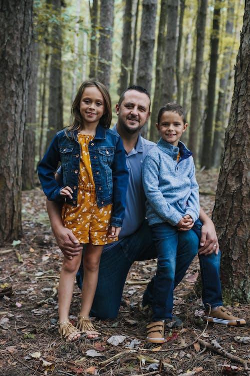 Happy man with children in forest