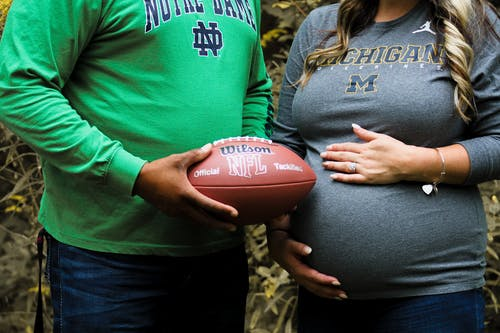 Crop diverse pregnant couple with ball