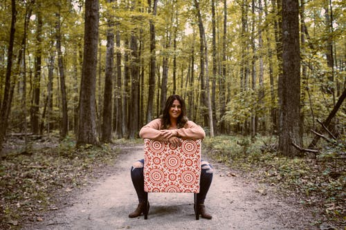 Attractive overweight woman on chair in forest