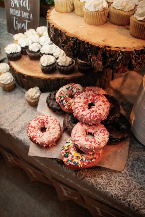 High angle of various tasty cupcakes and donuts on table in modern shop