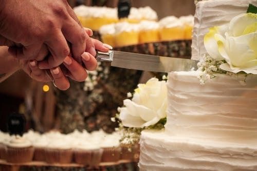 Crop faceless newlywed couple holding knife and cutting tasty cake together during wedding banquet
