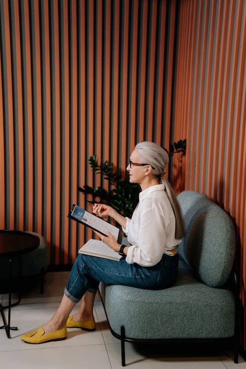 白色長袖襯衫和藍色牛仔牛仔褲,坐在灰色的沙發椅子上的女人