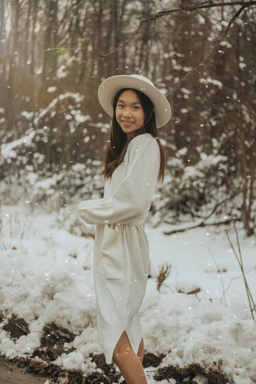 Happy Asian woman in dress smiling in winter forest